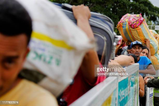 People cross the Simon Bolivar international bridge to Venezuela, on October 23, 2019 in Cucuta, Colombia, prior to its temporary closure by the...