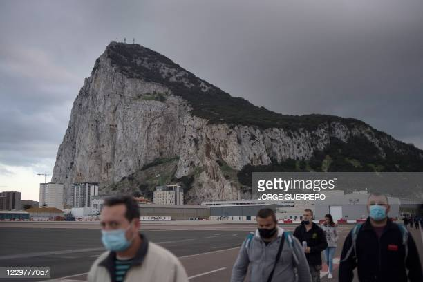 People cross the Spanish border of the British overseas territory of Gibraltar on November 24, 2020. - With its traditional British red phone boxes,...