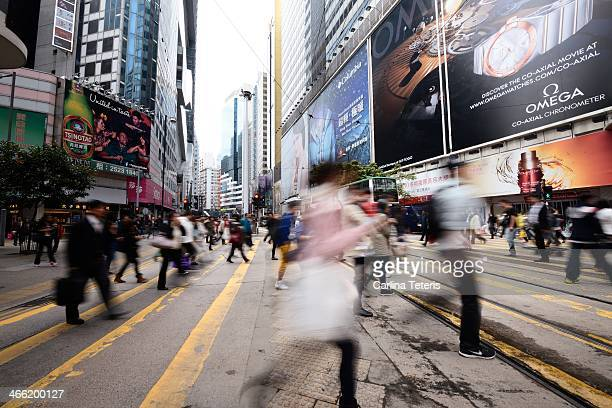 People cross the street at a yellow, marked cross walk in Central Hong Kong