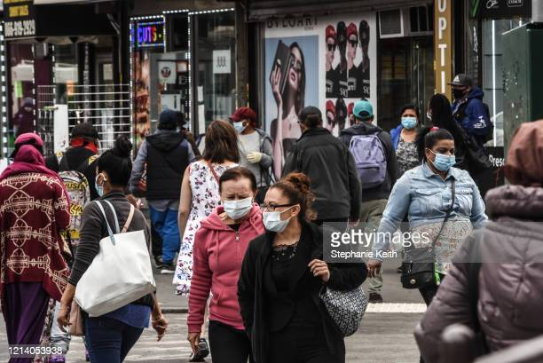 People cross the street on May 19, 2020 in the Jamaica neighborhood in the Queens borough in New York City. New York City is currently in its ninth...