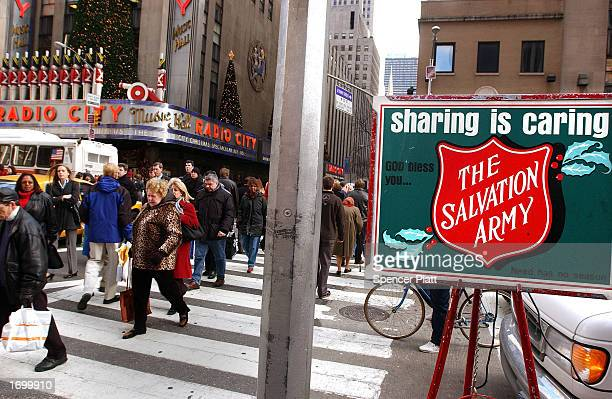 People cross the street past a Salvation Army sign near Radio City Music Hall December 23 2002 in New York City The Commerce Department reported...