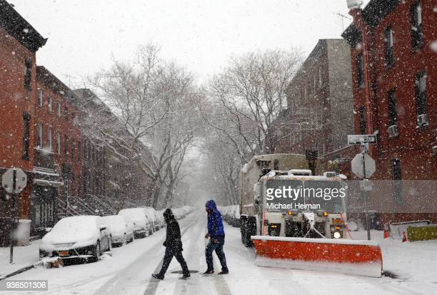 People cross the street past a snow plow while it snows on March 21 2018 in the Brooklyn borough of New York City Winter Storm Toby is expected to...