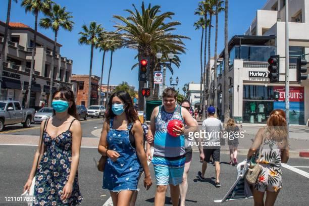 People cross the street, some wearing masks, amid the novel coronavirus pandemic in Huntington Beach, California on April 25, 2020. - Orange County...