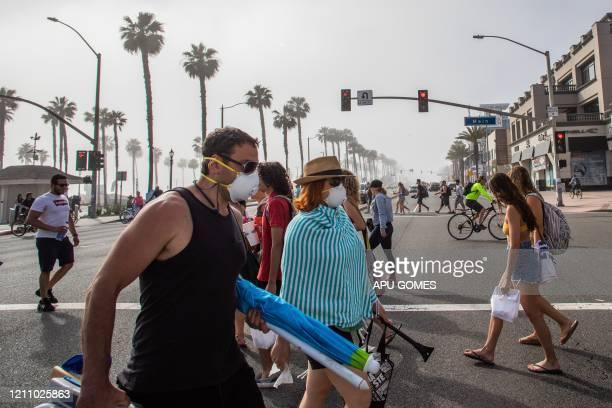 People cross the street some wearing masks amid the novel coronavirus pandemic in Huntington Beach California on April 25 2020 Orange County is the...