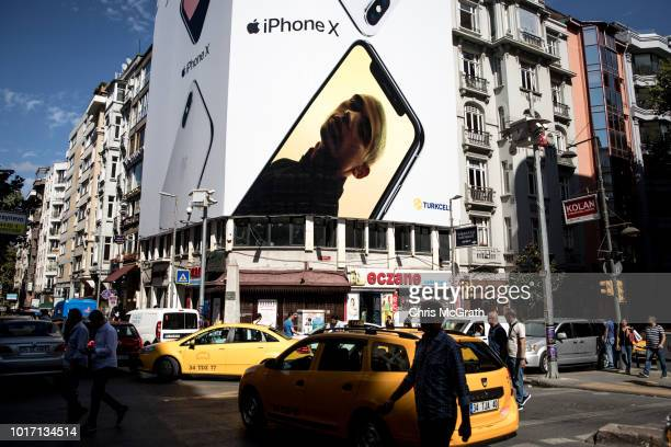People cross the street underneath a billboard advertising the Apple Iphone X on August 15 2018 in Istanbul Turkey The Turkish Lira recovered to...