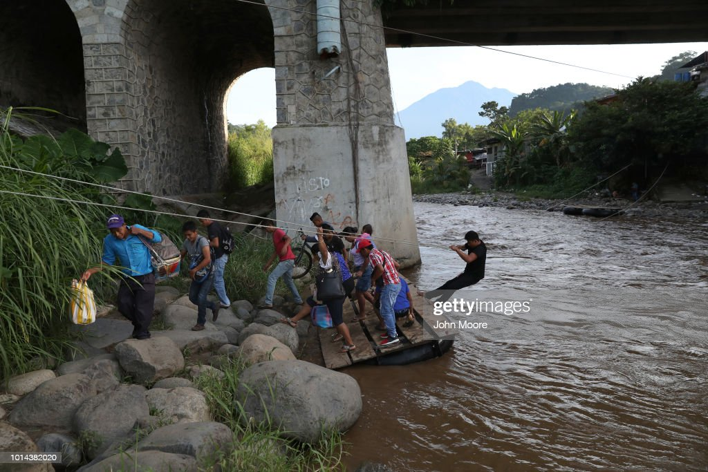 People cross the Suchiate River from Guatemala into Mexico on August 9, 2018 in Talisman, Mexico. The illegal crossing point is located just under the international bridge connecting the two countries, circumventing immigration and customs checkpoints.