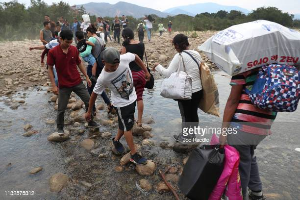 People cross through the low waters of the Táchira River near the Simón Bolívar international bridge which connects Cúcuta with the Venezuelan town...