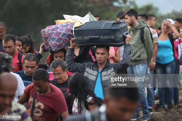 People cross through the low waters of the Táchira River near the Simón Bolívar international bridge on March 2 2019 in Cucuta Colombia The bridge...