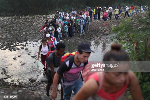 People cross through the low waters of the Táchira River near the Simón Bolívar international bridge on March 2, 2019 in Cucuta, Colombia. The...