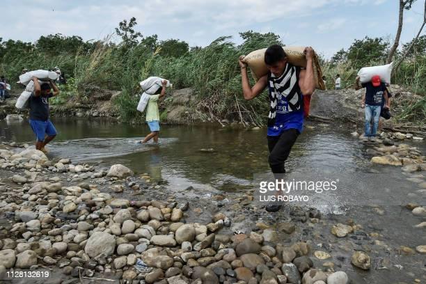 People cross through Trochas illegal trails across the Tachira river near the Simon Bolivar international bridge from San Antonio in Venezuela to...