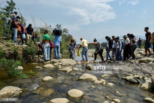 TOPSHOT People cross through Trochas illegal trails across the Tachira river near the Simon Bolivar international bridge from San Antonio in...
