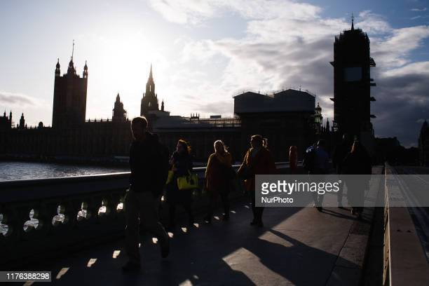 People cross Westminster Bridge in front of the Houses of Parliament as the sun begins to set in London England on October 17 2019 Prime Minister...