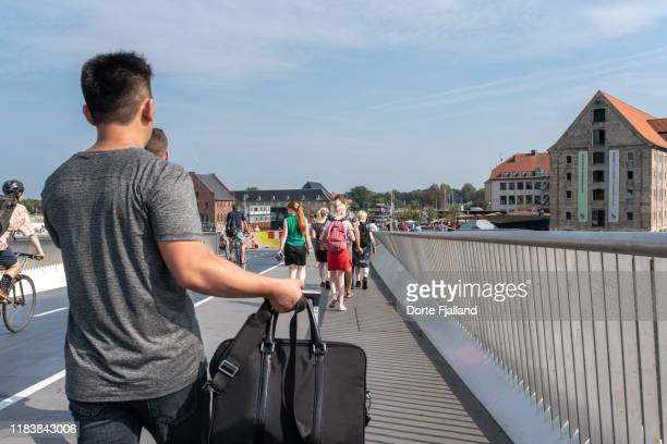 people crossing a bridge on foot on a sunny day in copenhagen - dorte fjalland stock pictures, royalty-free photos & images