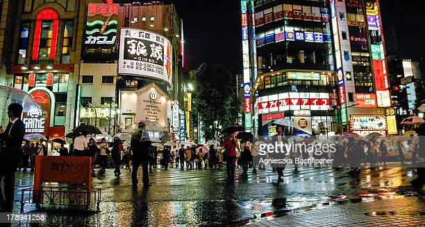 CONTENT] People crossing a road street lights and their reflections on a rainy night in Tokyo Japan