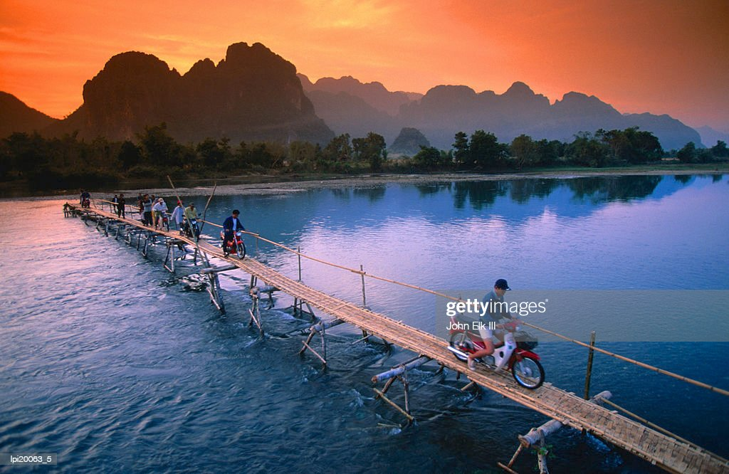 People crossing bridge across Nam Song River by motorbike, Vang Vieng, Laos : Stock Photo