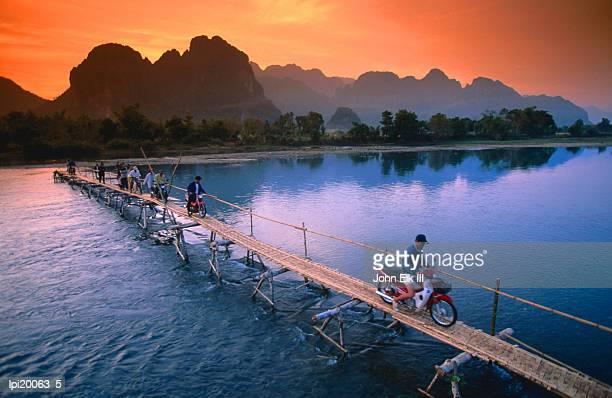 People crossing bridge across Nam Song River by motorbike, Vang Vieng, Laos