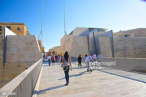 People crossing city gate on stone walkway, Malta