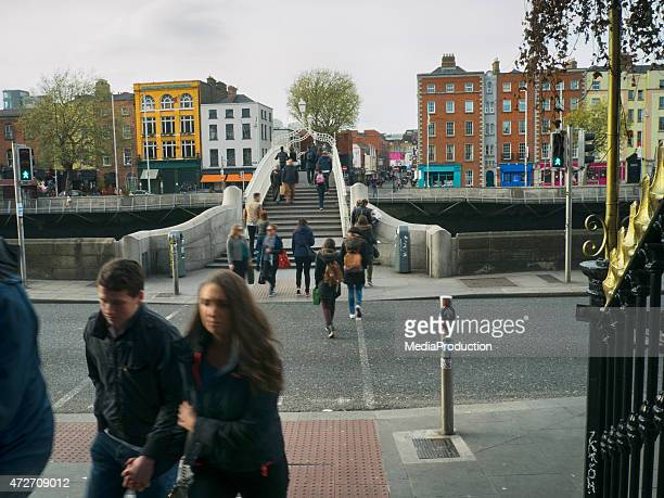 people crossing ha'penny bridge in dublin ireland over river liffey - henry street stock pictures, royalty-free photos & images
