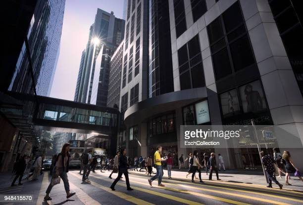 People crossing Queen's Road at a sunny morning in Hong Kong