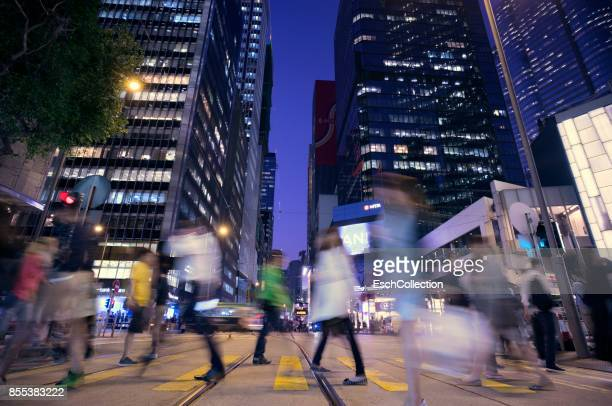 People crossing road at busy junction in Hong Kong at dusk