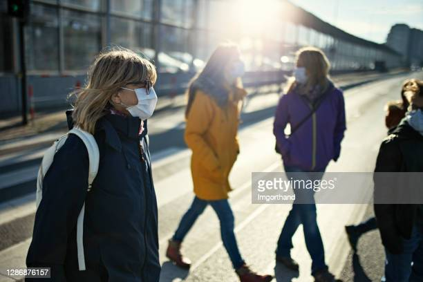 people crossing street during covid-19 pandemic - crowd stock pictures, royalty-free photos & images
