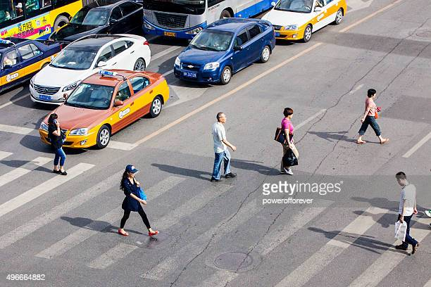 People crossing street in downtown Beijing, China