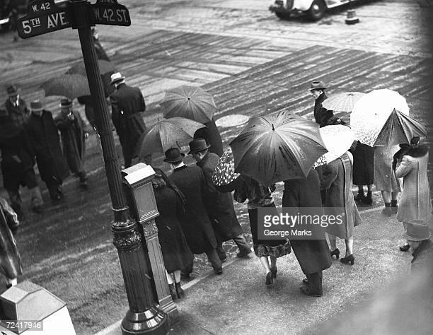 People crossing street in rain, (B&W), elevated view