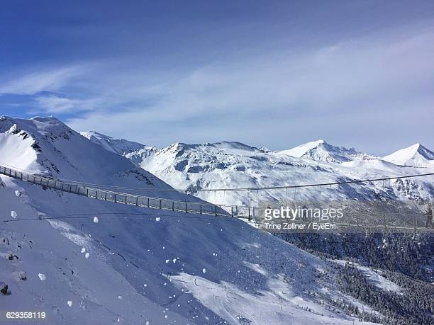 People Crossing Suspended Footbridge Over Snow Covered Mountains At Bad Gastein