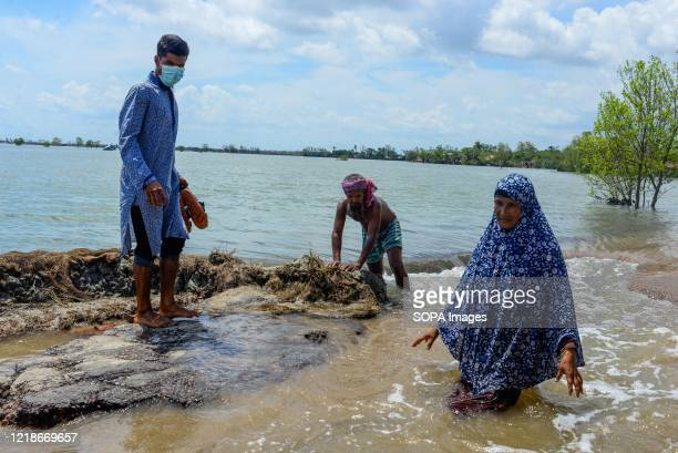 People crossing the broken flooded road after the landfall of cyclone Amphan during the aftermath. Thousands of shrimp enclosures have been washed...