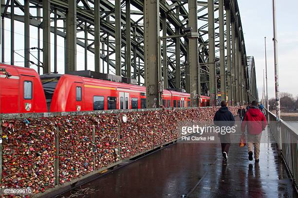 People crossing the Hohenzollern Bridge with padlocks on representing lovers' devotion as a train goes past Cologne Germany