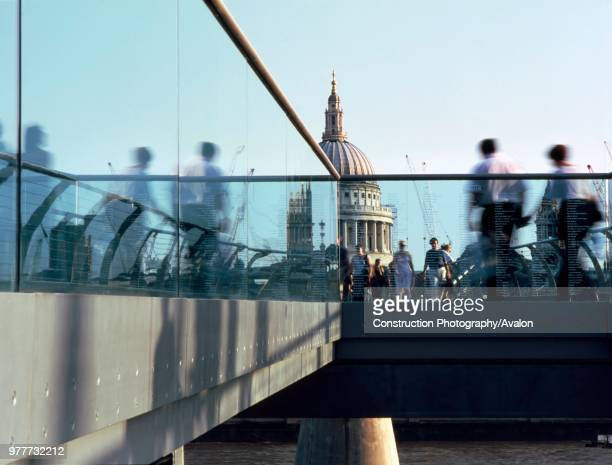 People crossing the Millennium footbridge with St Pauls Cathedral in background, London, United Kingdom, Bridge designed by Norman Foster and...