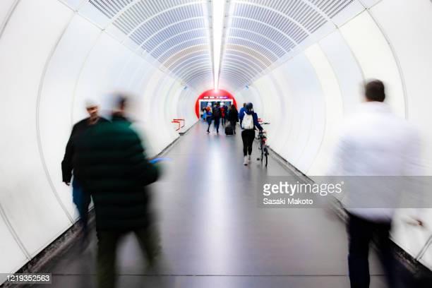 people crossing the passage of a subway station(vienna underground südtiroler platz station) - verkehrswesen stock-fotos und bilder