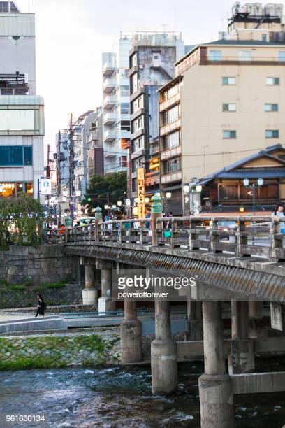 People crossing the Sanjo Bridge in the Kiyamachi District of Kyoto, Japan