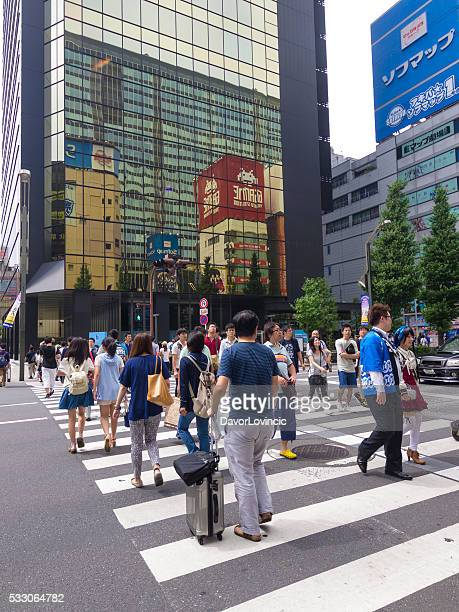 people crossing the street in akihabara in tokyo - chuo dori street stock photos and pictures
