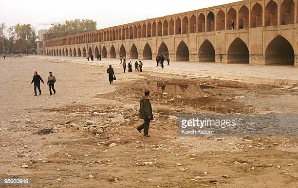 People crossing the the Zayanderud river on foot next to the SioSeh Pol bridge or Bridge of 33 Arches during a drought Isfahan Iran 30th November 2001