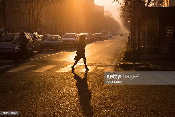 People crossing the Turin city streets on early morning with nice sunlight and silhouettes.
