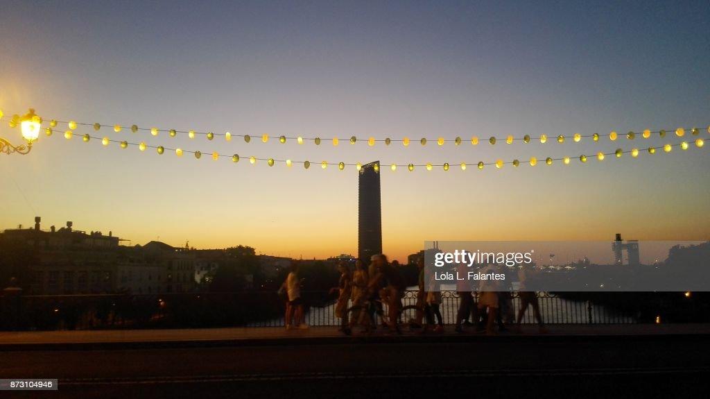 People crossing Triana bridge as night falls : Foto de stock