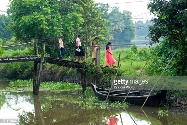 People crossing wooden bridge near Alappuzha Alleppey, Backwaters of Kerala, India
