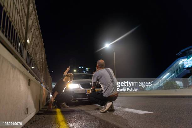 People crouch to find a cover during a missile alarm on May 15 in Tel Aviv, Israel. In the last week, cross-border fighting has escalated between...