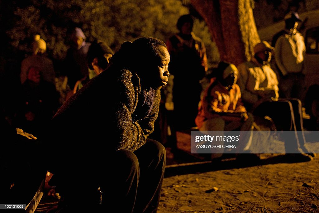 People crowd around a fire to keep warm as they watch a television set up outside for the 2010 World Cup football match between Brazil and North Korea at a home near Pretoria on June 15, 2010. The public viewing was possible after a local Afrikaaner offered the television to the community where no electricity has been available for six years. AFP PHOTO / Yasuyoshi CHIBA