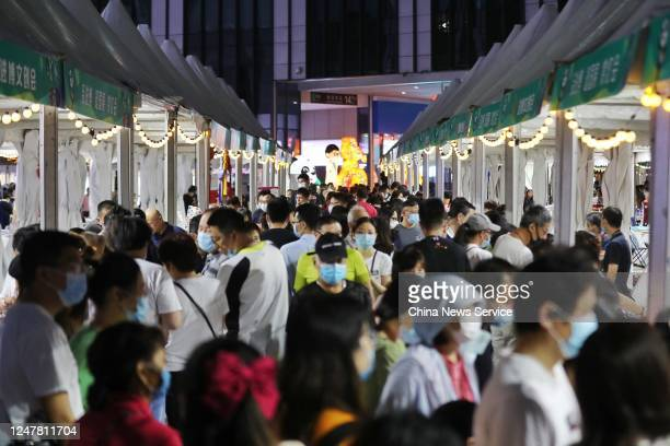 People crowd around street vendors during a night market at National Exhibition and Convention Center on June 6, 2020 in Shanghai, China.