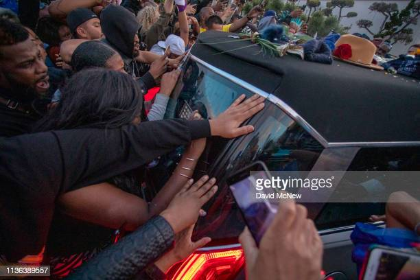 People crowd around the hearse carrying slain rapper Nipsey Hussle as it arrives to Angelus Funeral Home on April 11 2019 in Los Angeles California...