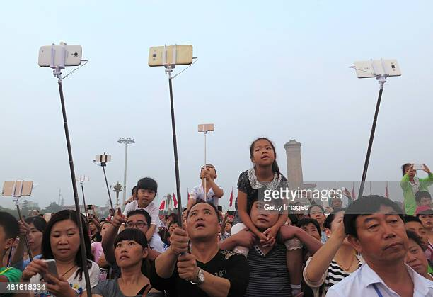 People crowd at Tiananmen Square use selfie sticks to take photos of halfmast to mourn the death of Chinese Communist Party elder Wan Li on July 22...