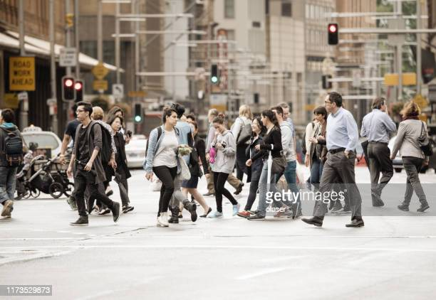 people crowd crossing street in central sydney - pedestrian stock pictures, royalty-free photos & images