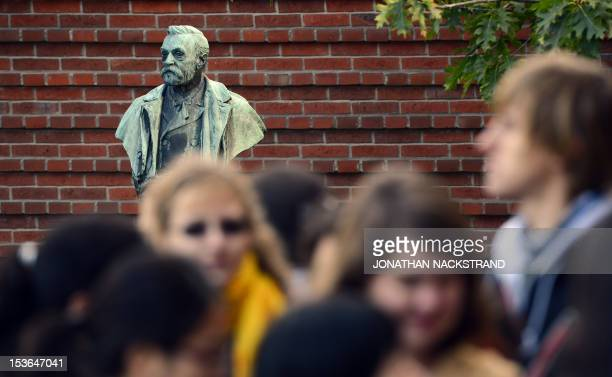 People crowd in front of a statue of Swedish inventor of dynamite Alfred Nobel prior to the awardings of the 2012 Nobel Prize in Medicine on October...