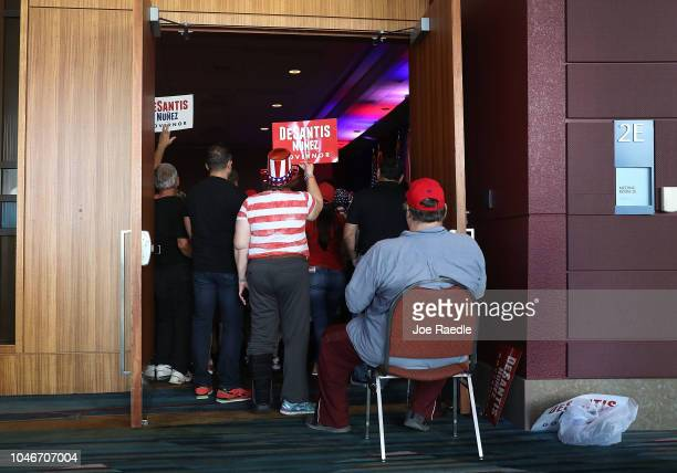 People crowd into a doorway as they listen to Republican gubernatorial candidate Ron DeSantis speak during a campaign rally at the Palm Beach County...