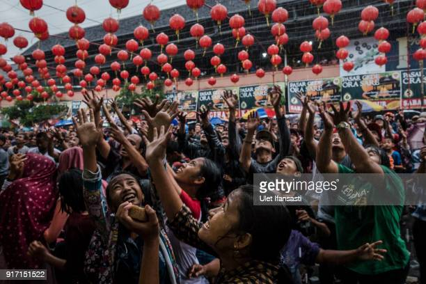 People crowd on the street as they scramble for Chinese sweetcakes during Grebeg Sudiro festival on February 11 2018 in Solo City Central Java...