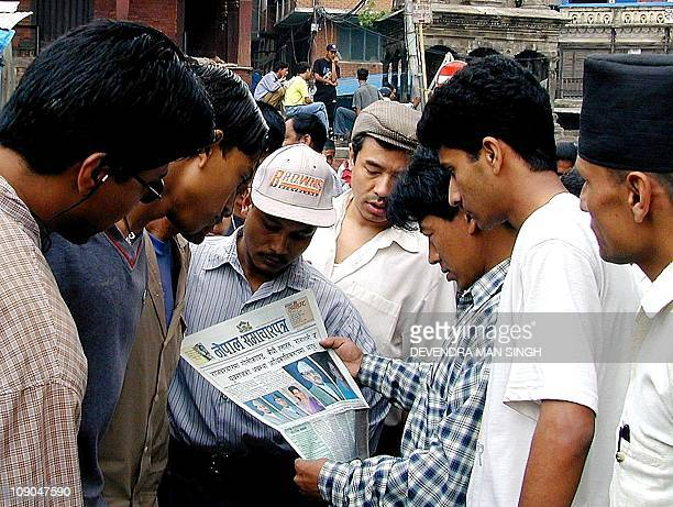 People crowd round to read a newspaper reporting the massacre of the Nepalese Royal family in Kathmandu 02 June 2001 King Birendra of Nepal and Queen...