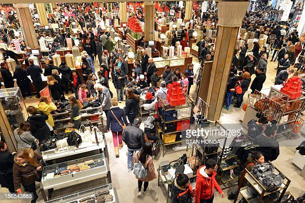 People crowd the first floor of Macy's department store as they open at midnight on November 23 2012 in New York to start the stores' 'Black Friday'...
