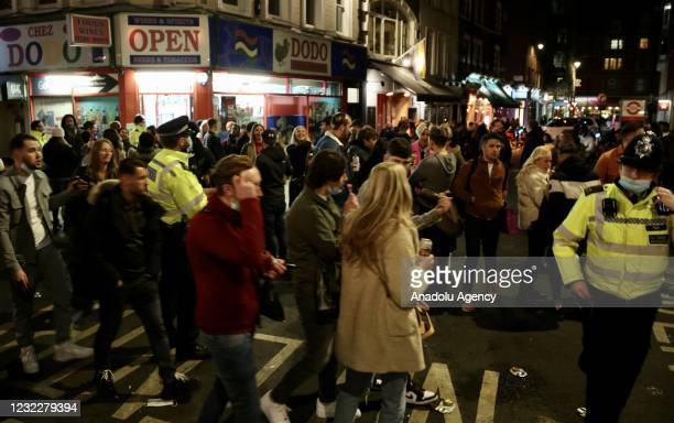 People crowd the Soho area after restaurants and pubs, which were closed within the nationwide lockdown imposed to stem the spread of coronavirus ,...